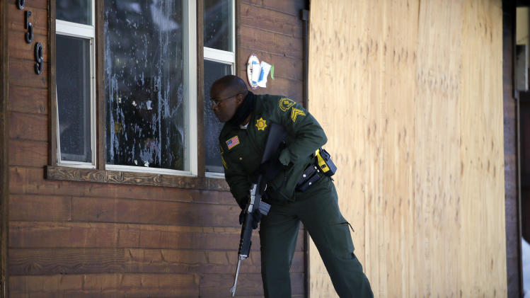 San Bernardino County Sheriff's officer Ken Owens searches a home for the former Los Angeles police officer Christopher Dorner in Big Bear Lake, Calif, Sunday, Feb. 10, 2013. The hunt for the former Los Angeles police officer suspected in three killings entered its fourth day in the snow-covered mountains on Sunday, a day after the police chief ordered a review of the disciplinary case that led to the fugitive's firing and new details emerged of the evidence he left behind. (AP Photo/Jae C. Hong)