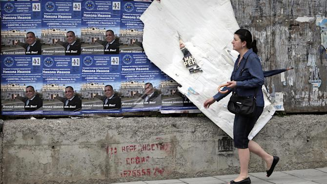 A woman passes by torn out election campaign posters in Sofia, Thursday, May 9, 2013.  A deeply fragmented Bulgaria heads into parliamentary elections Sunday, as frustration grows over the widening gap between once giddy hopes linked to EU membership and today's sobering reality. (AP Photo/Valentina Petrova)