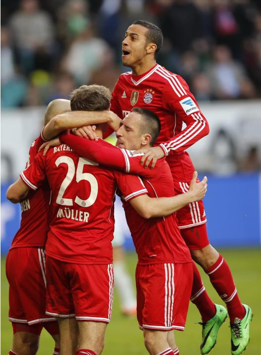 Bayern's Thomas Mueller is surrounded by teammates after he scores a goal against Wolfsburg during their German first division Bundesliga match in Wolfsburg