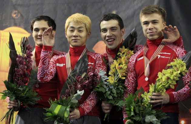 Second placed Russia's team celebrate on the podium after the men's 5000m relay final at the ISU World Short Track Speed Skating Championships in Debrecen