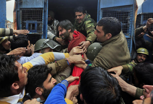 Indian policemen detain Jammu Kashmir Liberation Front (JKLF) chairman Yasin Malik, in red jacket, during a protest in Srinagar, India, Friday, March 7, 2014. Dozens of Muslim students from the disput