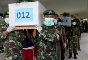 Indonesia soldiers carry coffins containing bodies…