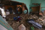 People stand in a house flooded by mud after a mountain landslide in Altotonga in Veracruz state, along Mexico's Gulf coast, September 16, 2013. REUTERS/Oscar Martinez