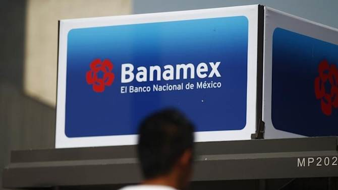 A man walks in front of a Banamex advertisement in Mexico City