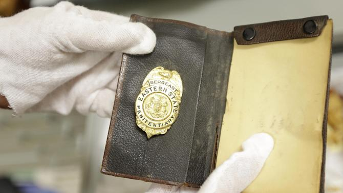 """In this Tuesday, March 12, 2013 photo, shown is a jailers badge at the Eastern State Penitentiary in Philadelphia. The defunct and decayed prison that serves as one of Philadelphia's quirkiest tourist attractions, plans to displaying dozens of never-before-seen artifacts for 10 days only in a """"pop-up museum."""" (AP Photo/Matt Rourke)"""