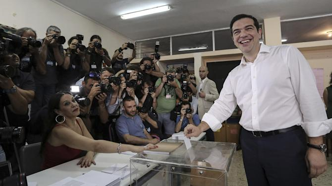 Greece's Prime Minister Alexis Tsipras, right, casts his vote at a polling station in Athens, Sunday, July 5, 2015.  Greeks were voting Sunday in a bailout referendum that will decide the country's future, with opinion polls showing people evenly split on whether to accept creditors' proposals for more austerity in exchange for rescue loans or defiantly reject the deal. (Giannis Liakos/InTime News via AP) GREECE OUT