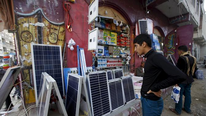 A man looks at solar panels and lamps amid a severe shortage of electric power in Yemen's capital Sanaa