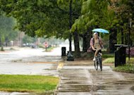 A cyclist holds an umbrella as he rides through the Purdue University campus in West Lafayette, Ind. as the remnants of Hurricane Isaac&#39;s rain falls on Sunday, Sept. 2, 2012. (AP Photo/The Journal & Courier, Brent Drinkut)