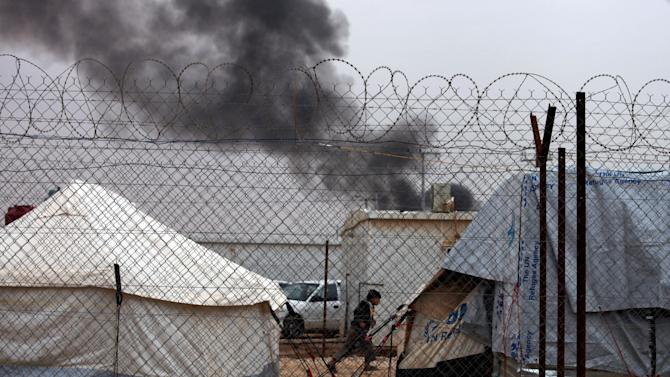 A Syrian refugee boy runs after a tent caught on fire at the Zaatari Syrian refugees camp , in Mafraq, near the Syrian border, Jordan, Monday, Jan. 28, 2013. A refugee tent caught on fire, and the family living in it was evacuated by the refugees. UN officials say a spike in Syrian refugees fleeing to Jordan in the past week has seen about 21,000 new arrivals with Jordan's Zaatari refugee camp now hosting about 83,000 registered refugees.  (AP Photo/Mohammad Hannon)