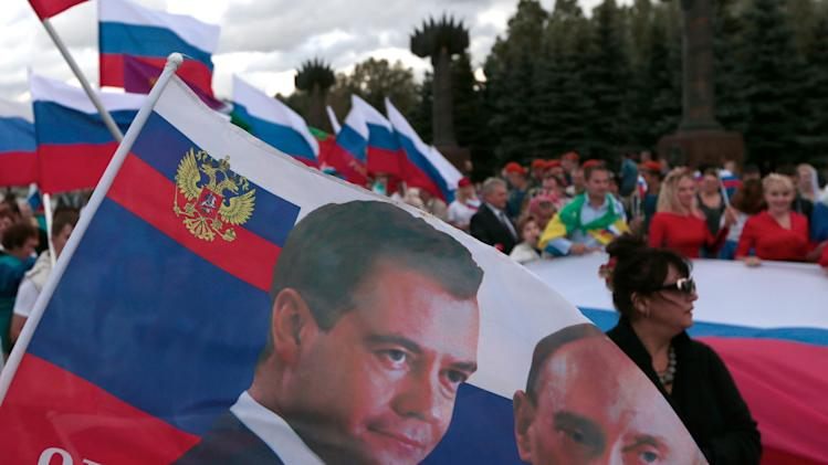A Russian flag with portraits of President Vladimir Putin and Prime Minister Dmitry Medvedev is held by demonstrators during celebrations marking National Flag Day in Moscow, Friday, Aug. 22, 2014. The holiday, introduced in 1994, is marked annually to commemorate the first time in 1991 when three-color flag was hoisted over the Russian government building to replace the Soviet hammer and sickle flag after Russia's failed 1991 coup. (AP Photo/Ivan Sekretarev)