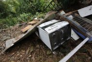 Broken appliances and building material lay in a heap outside a house at Scorpion Alley, as part of the destruction from a mudslide following heavy showers caused by the passing of Tropical Storm Isaac, in Carenage, about 10 km (6 miles) west of the capital Port-of-Spain August 23, 2012. REUTERS/Andrea De Silva