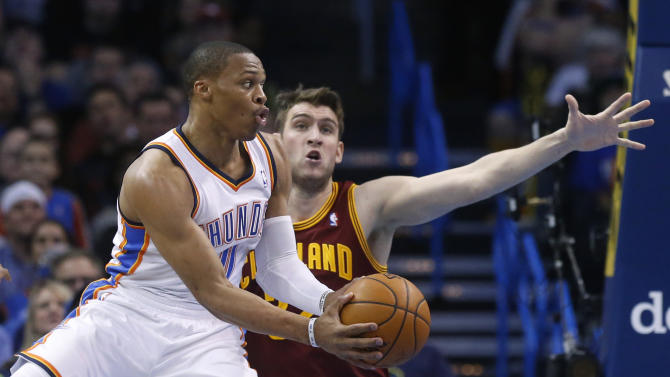 Oklahoma City Thunder guard Russell Westbrook (0) passes off in front of Cleveland Cavaliers center Spencer Hawes in the second quarter of an NBA basketball game in Oklahoma City, Wednesday, Feb. 26, 2014. (AP Photo/Sue Ogrocki)