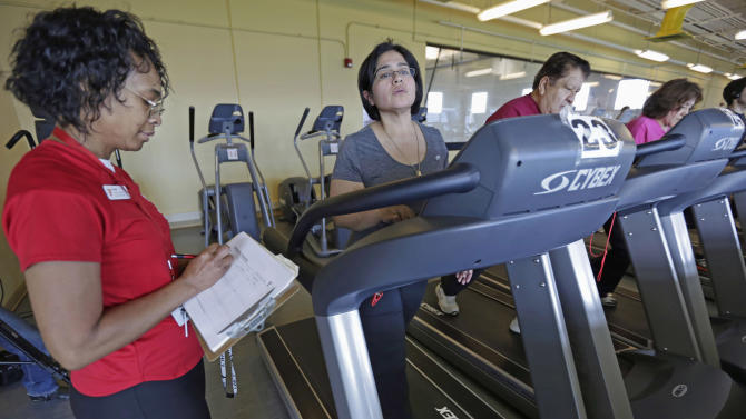 In this March 26, 2013 photo, Aidee Diaz, 36, center, exercises with personal trainer Angela Appleton, left, at the Rauner Family YMCA on Chicago's South Side. Diaz has lost 100 pounds since a simultaneous robotic kidney transplant and obesity surgery in July 2012 at the University of Illinois Hospital & Health Sciences System in Chicago. Diaz says the YMCA workouts are helping her get in shape. (AP Photo/M. Spencer Green)