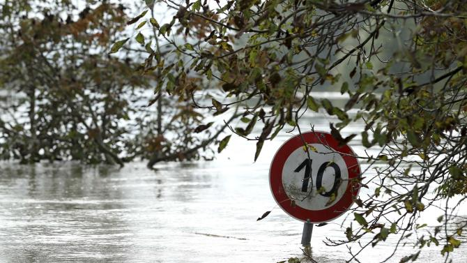 A traffic sign is partially submerged in flood water at Letovanic village