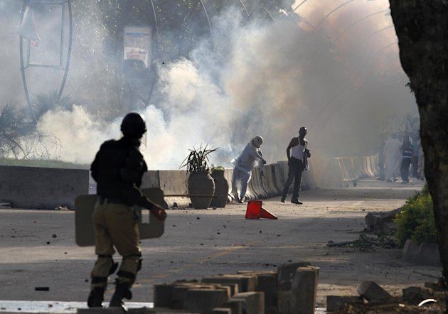 A Pakistani protestor hurls back a tear gas canister fired by police during clashes that erupted as protestors tried to approach the U.S. embassy, Friday, Sept. 21, 2012 in Islamabad, Pakistan. Protests by tens of thousands of Pakistanis infuriated by an anti-Islam film descended into deadly violence on Friday, with police firing tear gas and live ammunition in an attempt to subdue rioters who hurled rocks and set fire to buildings in some cities. Four people were killed and dozens injured on a holiday declared by Pakistan&#39;s government so people could rally against the video. (AP Photo/Anjum Naveed)