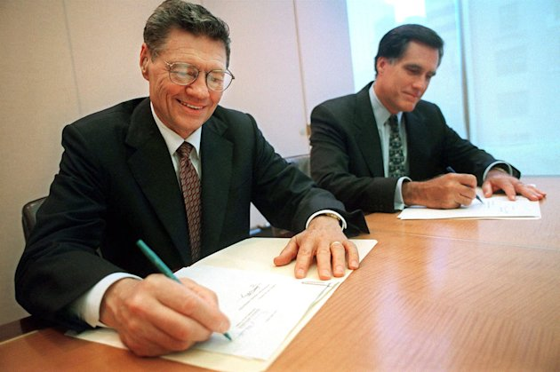 "FILE - In this Sept. 25, 1998, photo released by Domin's Pizza, Thomas S. Monaghan, founder and chairman of Domino's Pizza, Inc., left, and Mitt Romney, managing director of Bain Capital, Inc., sign an agreement for Monaghan to sell a ""significant portion"" of his stake in the company to Bain Capital in New York. Republican presidential candidate Mitt Romney has said he had no active role in Bain Capital, the private equity firm he founded, after he exited in February 1999 to take over Salt Lake City's Winter Olympics bid. But according to Bain associates and others familiar with Romney's actions at the time, he stayed in regular contact with his partners over the following months, tending to his partnership interests and negotiating his separation from the company. (AP Photo/Domino's Pizza, Scott Gries, file)"
