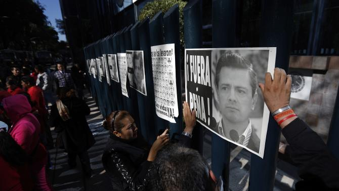 "Demonstrators hang posters reading ""Pena Out"" at the fence of Mexico's Attorney General office during a protest in support of the 43 missing students l in Mexico City"