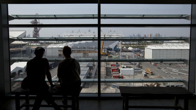 Two people   sit by a window overlooking the London 2012 Olympic Park as work continues to make it ready for the opening ceremony and the competing athletes in London,Tuesday, May 29, 2012. With just 59 day to go to the beginning of the games on July 27 all the main stadia are complete and much of the work now being done is cosmetic. (AP Photo/Alastair Grant)