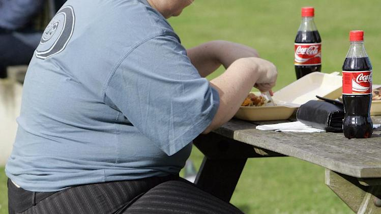 FILE- In this file photo dated Wednesday, Oct. 17, 2007, an overweight person eats in London, Wednesday, Oct. 17, 2007. Almost a third of the world population is now fat, and no country has been able to curb obesity rates in the last three decades, according to a new global analysis released Thursday May 29, 2014, led by Christopher Murray of the Institute for Health Metrics and Evaluation at the University of Washington, USA, and paid for by the Bill & Melinda Gates Foundation. Researchers reviewed more than 1,700 studies covering 188 countries covering over three decades and found more than 2 billion people worldwide classified as overweight or obese. The highest rates of obesity were found in the Middle East and North Africa, with the U.S. having about 13 percent of the world's fat population. (AP Photo/Kirsty Wigglesworth, FILE)