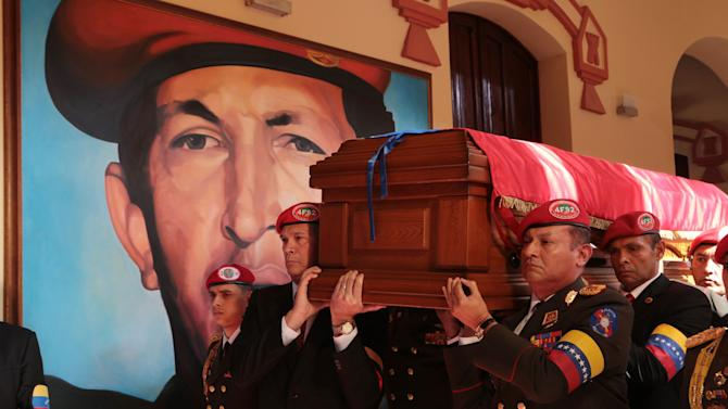In this photo released by the Miraflores Press Office, soldiers who served with Venezuela's late President Hugo Chavez carry his coffin inside the military museum, Chavez's final resting place, where a mural of Chavez covers a wall, in Caracas, Venezuela, Friday, March 15, 2013. Chavez, 58, died of an undisclosed type of cancer on March 5. (AP Photo/Miraflores Press Office)