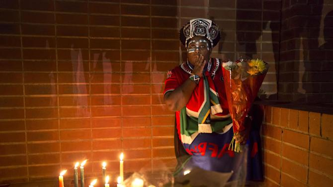 Soweto resident Joy Chauke pauses as she lays flowers outside the old house of Nelson Mandela in Soweto, Johannesburg, South Africa Friday, Dec. 6, 2013. Flags were lowered to half-staff and people in black townships, in upscale mostly white suburbs and in South Africa's vast rural grasslands commemorated Nelson Mandela with song, tears and prayers on Friday while pledging to adhere to the values of unity and democracy that he embodied. (AP Photo/Ben Curtis)