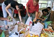 <p>People fill up bags with fruits and vegetables for distribution to needy people in a working class neighbourhood of Madrid on June 1. Spain was thrown back onto the front line of the eurozone debt crisis on Monday as its long-term borrowing rate shot above seven percent, dashing hopes for a respite after the Greek election.</p>