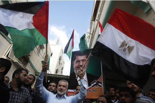 Gaza's Hamas Prime Minister Ismail Haniyeh, center, waves the Palestinian and Egyptian flags during celebrations of the victory of Mohammed Morsi in the Egyptian presidential elections, in Gaza City, Sunday, June 24, 2012. The Muslim Brotherhood victory in Egyptian presidential elections raises fears in Israel that the historic 1979 peace agreement with its southern neighbor is now in danger, a scenario that would have grave implications for regional security. But in the Hamas-ruled Gaza Strip, ecstatic residents flock to the streets, fire guns into the air and distribute candies in celebration, hopeful that Mohammed Morsi's election will usher in a new era for the blockaded seaside territory. (AP Photo/Hatem Moussa)