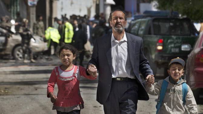 An Afghan man directs his children away from the scene where a suicide car bomber attacked a NATO convoy in Kabul, Afghanistan, Thursday, May 16, 2013. A Muslim militant group, Hizb-e-Islami, claimed responsibility for the early morning attack, killing at least six people in the explosion and wounding more than 30, police and hospital officials said. The powerful explosion rattled buildings on the other side of Kabul and sent a pillar of white smoke into the sky in the city's east. (AP Photo/Anja Niedringhaus)