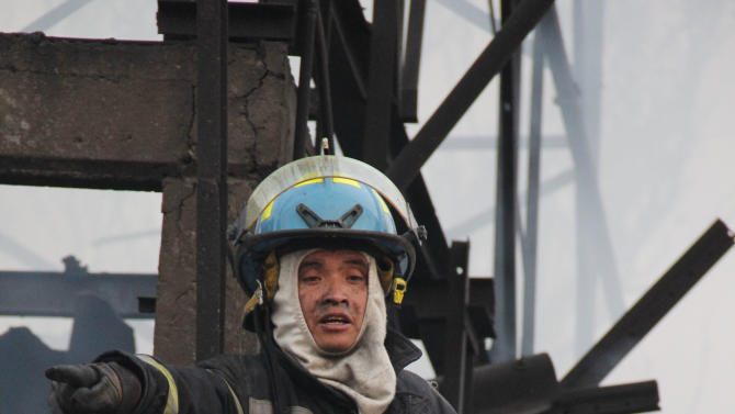 A firefighter gestures as he works to put out a fire in a home after a gas tanker truck exploded on a nearby highway in the Mexico City suburb of Ecatepec early Tuesday, May 7, 2013.  The blast killed and injured dozens, according to the Citizen Safety Department of Mexico State. Officials did not rule out the possibility the death toll could rise as emergency workers continued sifting through the charred remains of vehicles and homes built near the highway on the northern edge of the metropolis. (AP Photo/Gabriela Sanchez)