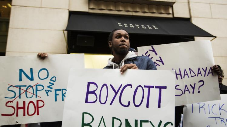 Demonstrators stand in front of a Barneys luxury department store of with signs decrying allegations that Barney's and Macy's stores have unfair security policies aimed at minorities in New York
