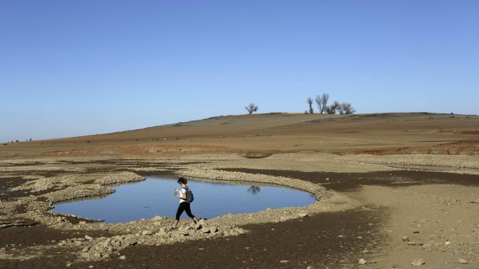 A visitor walks near the receding waters at Folsom Lake, which is 17 percent of its capacity, in Folsom