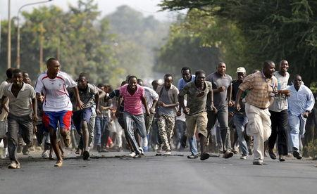 Protesters retreat during clashes with riot police in Burundi's capital Bujumbura