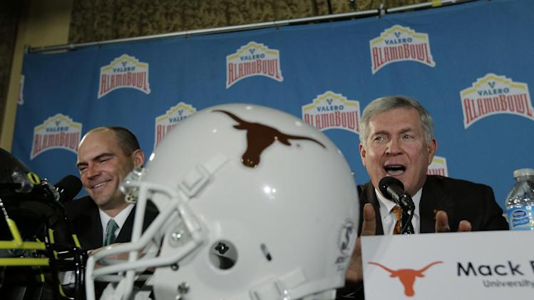Oregon coach Mark Helfrich, left, and Texas coach Mack Brown, right, take part in a Valero Alamo Bowl news conference, Thursday,  Dec. 12, 2013, in San Antonio. Texas and Oregon will play in the NCAA college football game Dec. 30