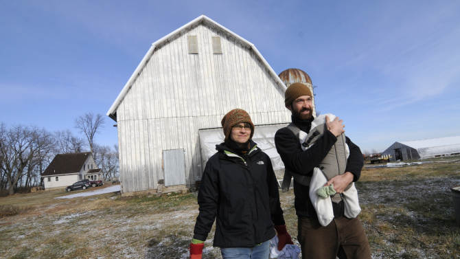 In this photo made Thursday, Dec. 1, 2011, Laura Frerichs, 31, is shown with husband Andy carrying infant son Eli on her organic farm outside of Hutchinson, Minn. Frerichs discovered her passion for farming about a year after she graduated from college with an anthropology degree and is among more people in their 20s and 30s going into farming. (AP Photo/Jim Mone)