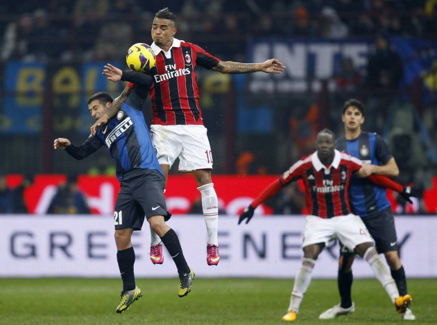 Inter Milan's Gargano jumps for the ball with AC Milan's Boateng during their Italian Serie A soccer match in Milan