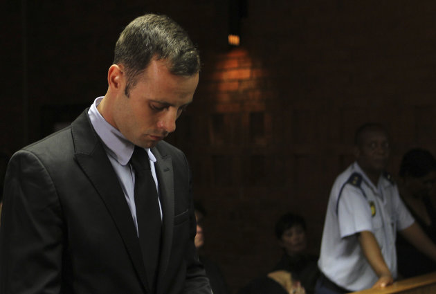 Olympic athlete Oscar Pistorius stands inside the court as a police officer looks on during his bail hearing at the magistrate court in Pretoria, South Africa, Wednesday, Feb. 20, 2013. A South African judge says defense lawyers will need to offer &quot;exceptional&quot; reasons to convince him to grant bail for Oscar Pistorius, when a hearing resumes Wednesday. (AP Photo/Themba Hadebe)
