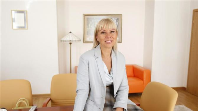 Minister for regional development Bienkowska smiles as she poses for a picture at her office in Warsaw