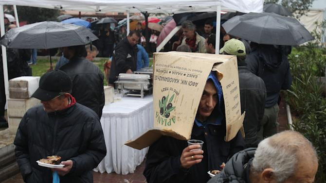 """A man uses a cardboard carton to protect himself from the rain as other people line up for free meat lunches under rainfall in Athens on Thursday, March 7, 2013. It's called """"Barbecue Thursday"""" _ a raucous pre-Easter celebration for meat lovers. But this year's Tsiknopempti festivities, a fixture of the Carnival season, coincided with the Greek Statistical Authority announced unemployment in Greece has dipped marginally to 26.4 percent, according to data for December. (AP Photo/Thanassis Stavrakis)"""