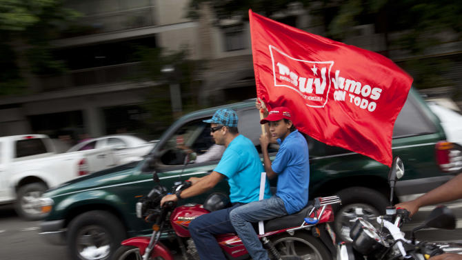 """A supporter of Venezuela's President Hugo Chavez holds a flag that reads in Spanish: """"We're going all out,"""" while taking part in a campaign caravan through the streets of Caracas, Venezuela, Friday, Sept. 28, 2012. Venezuela's presidential election is scheduled for Oct. 7. (AP Photo/Rodrigo Abd)"""