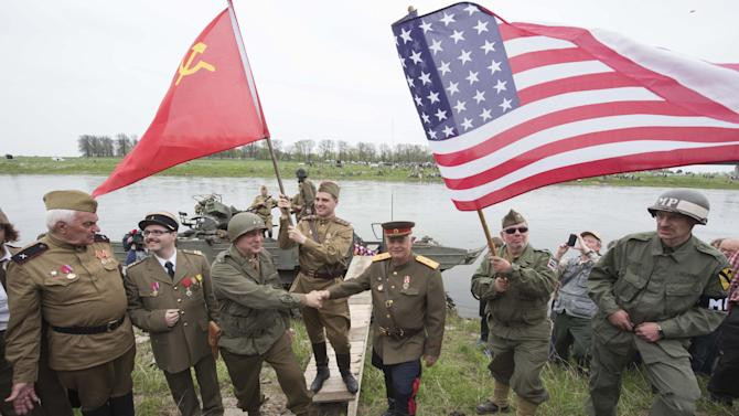 Amateur actors re-enact the link-up of Soviet and American troops during the 70th anniversary of the Elbe Day in Torgau, eastern Germany, Saturday, April 25, 2015. The WW II link-up of US and Soviet Forces occurred here at the river Elbe on April 25, 1945. (AP Photo/Jens Meyer)