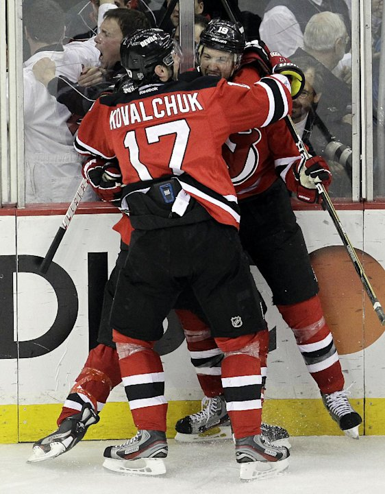 New Jersey Devils' Travis Zajac, right, celebrates with teammate Ilya Kovalchuk, of Russia, and another player after Zajac's game-winning goal in overtime against the Florida Panthers in Game 6 of a f
