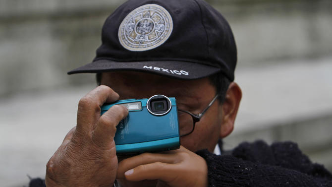 In this photo taken Sept. 7, 2011, Rodrigo Telon Yucute, a former guerrilla fighter during the civil war in the 1980's in his home country of Guatemala who lost his left forearm and his eyesight was destroyed after a land mine exploded beneath him, prepares to take a photograph of a a couple leaning back on a park bench in Mexico City Sept. 7, 2011. He is one of 30 visually impaired or blind people learning photography with the help of the Mexico City foundation Ojos Que Sienten, or Eyes That Feel. (AP Photo/Marco Ugarte)