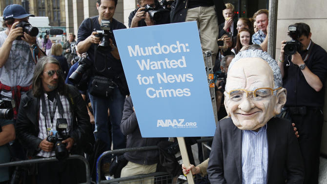 "A protestor wearing a Rupert Murdoch mask is photographed by media outside parliament in London, Tuesday, July 19, 2011. Britain's Conservative Party says a former News of the World executive may have given the prime minister's former communications chief advice before the 2010 national election. The Conservative Party said Neil Wallis, who was arrested last week in Britain's phone hacking scandal, ""may have provided Andy Coulson with some informal advice on a voluntary basis before the election."" (AP Photo/Kirsty Wigglesworth)"