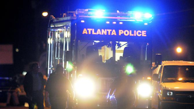 Law enforcement personnel investigate the scene of an Atlanta Police Department helicopter crash early Sunday, Nov. 4, 2012, that killed two officers aboard the aircraft when it crashed near a shopping center late Saturday, Nov. 3, 2012. (AP Photo/David Tulis)