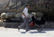 A man transports an ill woman on a cart along a street in Aleppo September 9, 2013. REUTERS/Muzaffar Salman