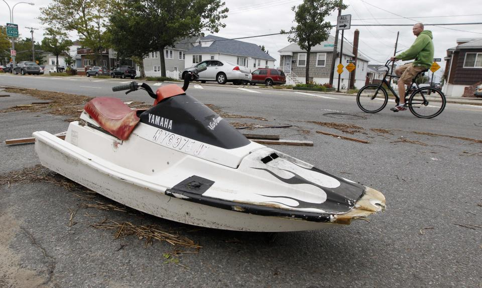 A bicyclist pedals past a wave runner sitting in the road following the effects of Tropical Storm Irene in the Broad Channel neighborhood of the Queens borough of New York, Sunday, Aug. 28, 2011.  The Broad Channel neighborhood experienced flooding during the storm surge earlier in the day.  (AP Photo/Charles Krupa)