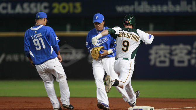 CORRECTS NAMES OF SOUTH KOREAN PLAYERS  - Australia's James Beresford (9) is forced out at first base by South Korea's first baseman Lee Seung-yeop, center,  and pitcher Song Seung-jun in the first inning of their World Baseball Classic first round game at the Intercontinental Baseball Stadium in Taichung, Taiwan, Monday, March 4, 2013. (AP Photo/Wally Santana)