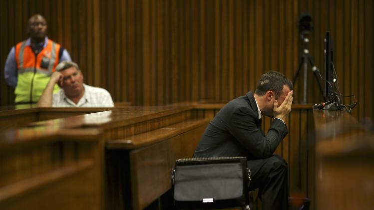 Olympic and Paralympic track star Oscar Pistorius reacts in the dock during his trial for the murder of his girlfriend Reeva Steenkamp, at the North Gauteng High Court in Pretoria