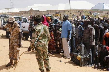 Military personnel help to organise returnees during an evacuation of Nigerian returnees from Niger, at a camp for displaced people in Geidam