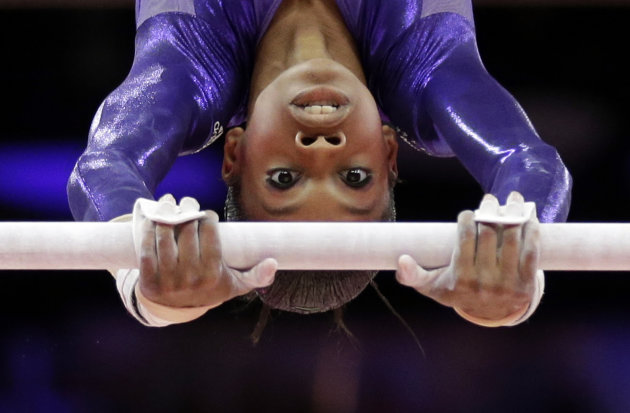 U.S. gymnast Gabrielle Douglas performs on the uneven bars during the Artistic Gymnastics women's qualification at the 2012 Summer Olympics, Sunday, July 29, 2012, in London. (AP Photo/Gregory Bull)